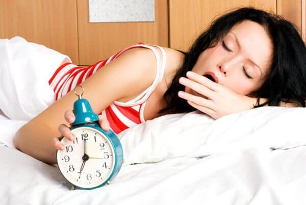жінка вимикає будильний