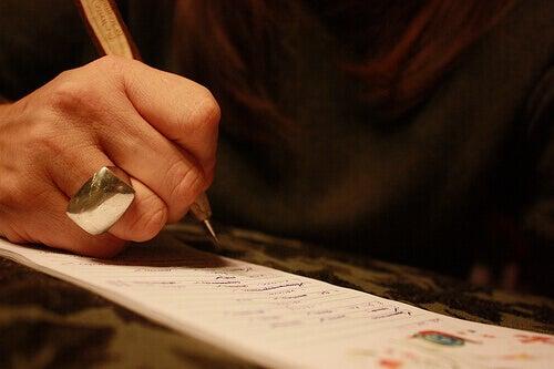 жінка тримає ручку та пише