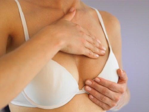 жінка проводить самоогляд молочної залози
