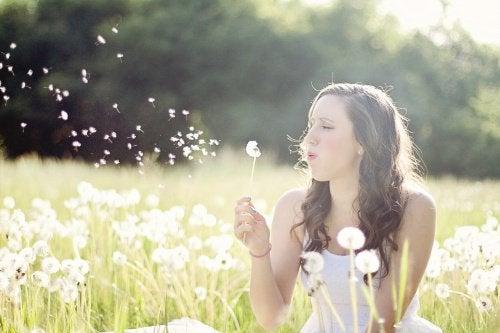 дівчина здуває білу кульбабу