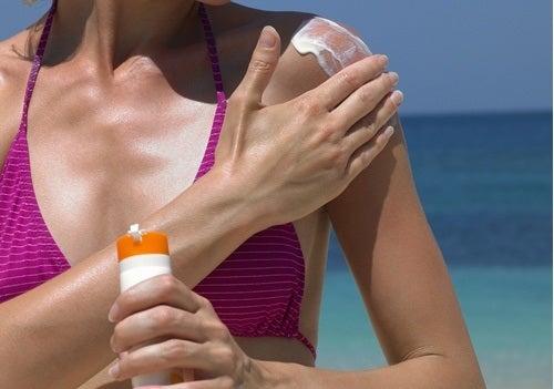 жінка мастись плечі сонцезахисним кремом