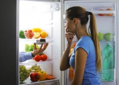 дівчина перед відкритим холодильником