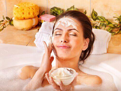 жінка робить пілінг обличчя в ванній