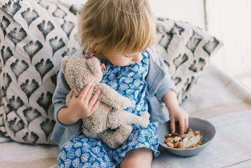 дитина сидить з іграшкою