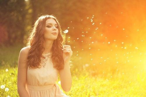 дівчина здуває білий цвіт кульбаби