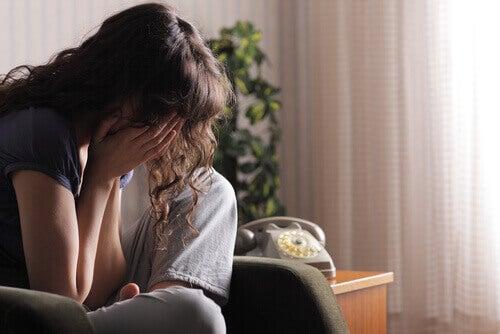 жінка сидить і закриває руками обличчя