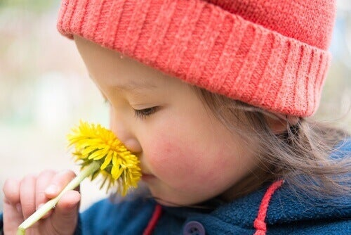 дитина нюхає квітку кульбаби