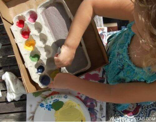 дівчинка змішує фарби за допомогою коробки від яєць