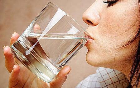 дівчина п'є воду зі склянки