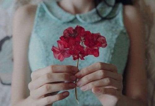дівчина тримає квітку