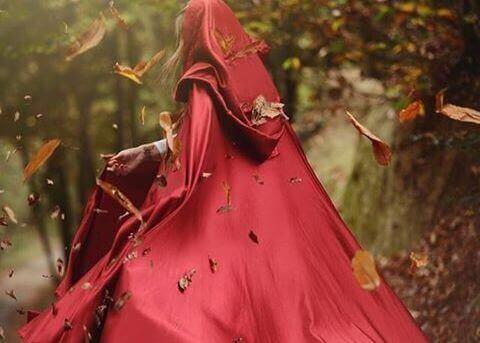 жінка у червоному плащі у лісі