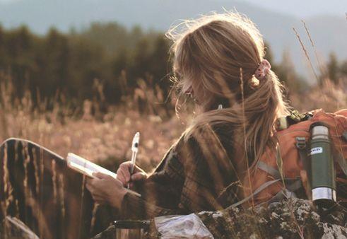 дівчина лежачи пише у полі