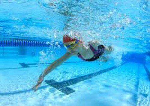 дівчина пливе під водою в басейні