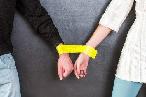 руки чоловіка та жінки зв'язані жовтою стрічкою