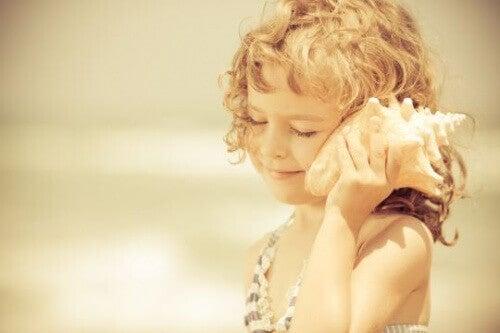 дитина тримає біля вуха мушлю