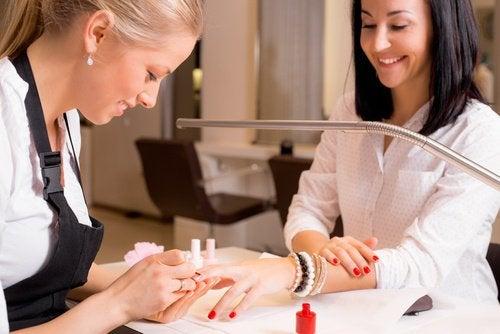 майстер манікюру фарбує нігті