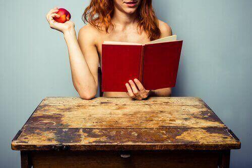 жінка читає книгу та їсть яблуко