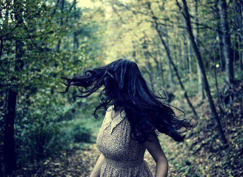 дівчина біжить через ліс, оглядаючись та відчуваючи страх