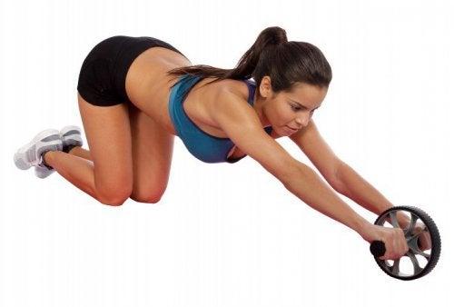 дівчина виконує вправу з колесом щоб позбутися жиру на животі