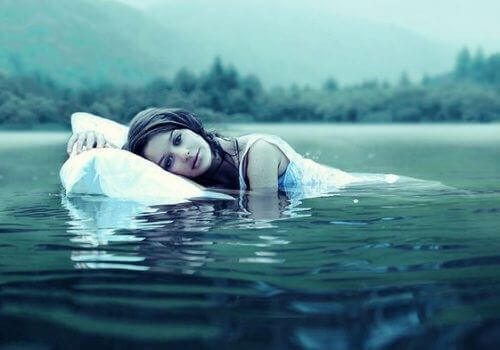 жінка з подушкою у воді
