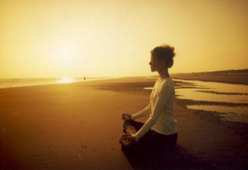 дівчина медитує на узбережжі