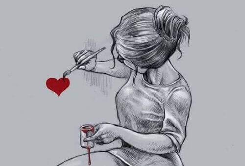 дівчина малює фарбою серце