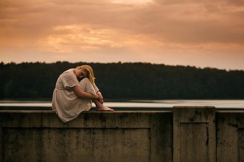 дівчина сидить на бетонній огорожі