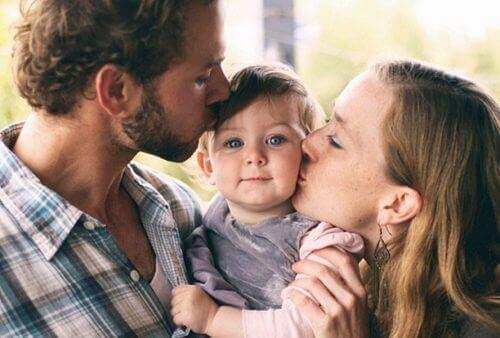 батьки цілують дитину