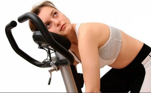 втомлена жінка на велотренажері