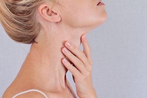 жінка торкається своєї шиї