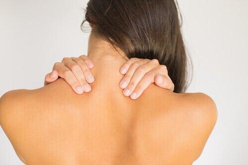 жінка тримається за плечі