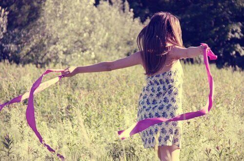 дівчина в полі з рожевою стрічкою