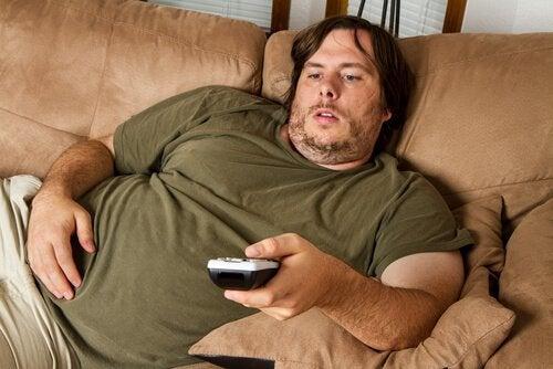 товстий чоловік лежить на канапі
