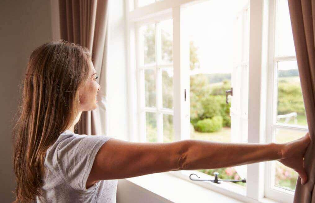 жінка дивиться у відкрите вікно