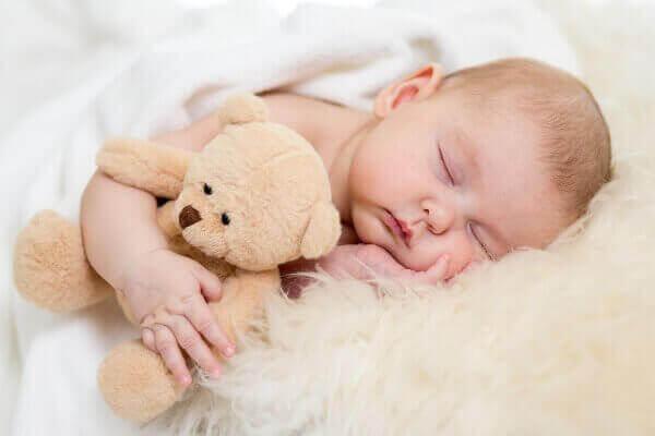 малюк спить з іграшкою