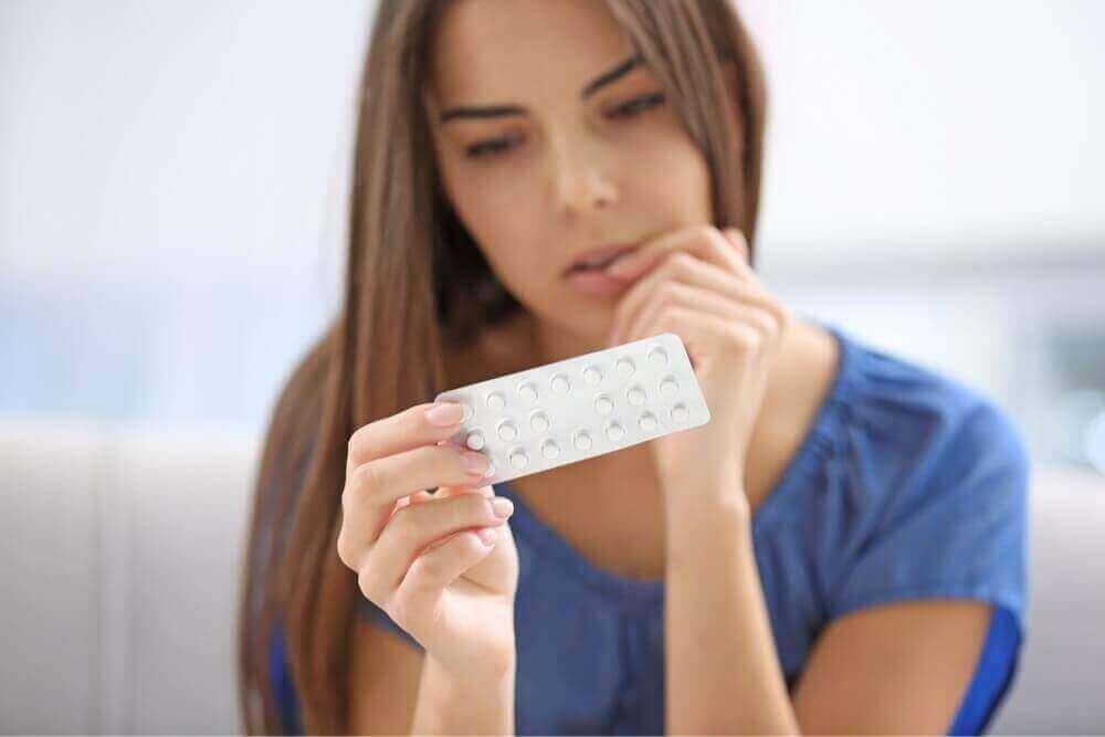 дівчина дивиться на таблетки