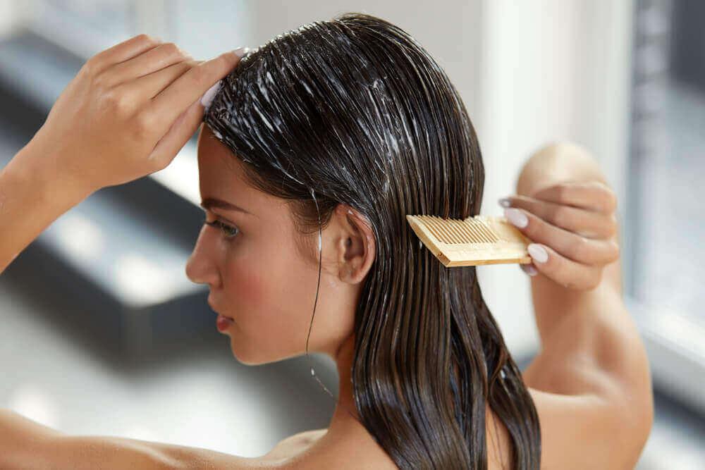 дівчина наносить маску на волосся